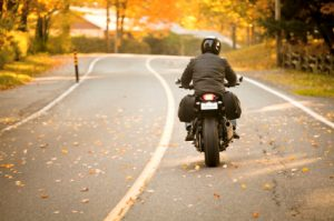 Motorcycle rider on fall roadway